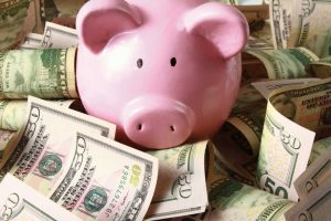 Pink Piggy-bank surronded by fifty-dollar bills